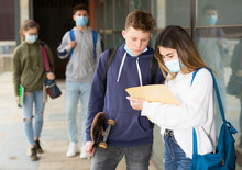 Focused Teenage Girl And Boy In Face Masks Talking About Homework After Lessons Near School Outdoors