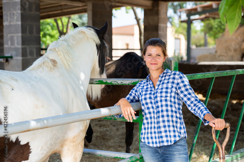 Obraz na plátne Happy confident young woman horses breeder standing near fencing of stable outdo