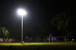 halogen lamp glowing on pole in empty ground at night