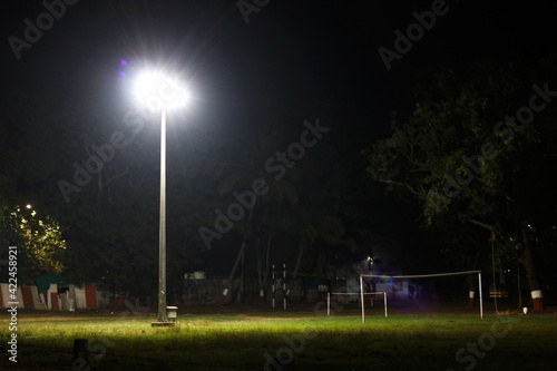 halogen lamp glowing on pole in empty ground at night Fototapeta