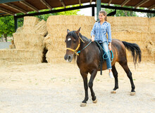 Positive Woman Farmer Riding A Horse. High Quality Photo