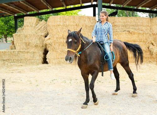 Fotografia, Obraz Positive woman farmer riding a horse. High quality photo
