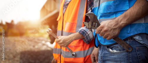 Hands of maintenance worker holding a wrench.