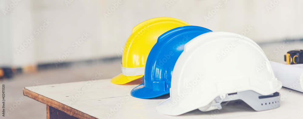 Fototapeta Construction hard hat safety tools equipment for workers in construction site for engineering protection head standard. Many hard hat helmet on row with copy space. Engineering Construction Concept
