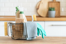 Basket With Brushes, Rags, Natural Sponges And Cleaning Products. Modern Kitchen Interior In The Background. House Cleaning Concept
