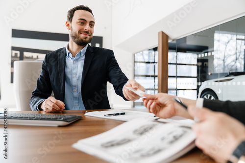 Smiling manager using customer's credit card while making deal