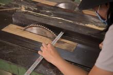 Carpenter Checking Saw Blade Using Metal Ruler