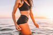 Anonymous sporty slim body of woman posing in calm sea at sunset in black sportswear. Liposuction, diet, abs