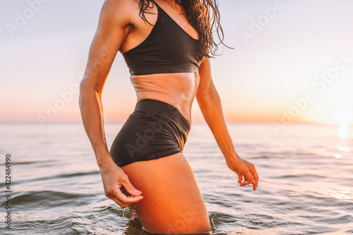 Fototapeta Anonymous sporty slim body of woman posing in calm sea at sunset in black sportswear. Liposuction, diet, abs obraz