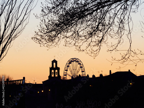 Silhouette of a village in fiestas with the church bell tower and a waterwheel against the light in Zamora.