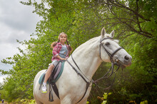 A Teenage Girl And A Horse In Nature Among Green Trees