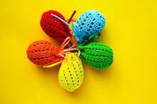 Easter Card. Colorful Knitted Egg Covers. Yellow Background. Packing Easter Eggs With Your Own Hands