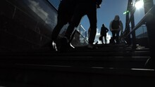 Legs Of A Young Man Climbing The Stairs From The Subway Up Against A Clear Blue Sky On A Sunny Day.