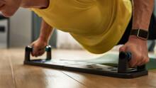 Muscular Man Pushing Up On Training System