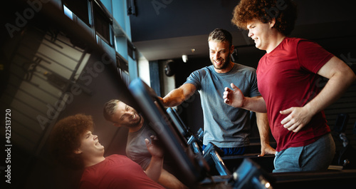 Fotografie, Obraz Overweight young man exercising gym with personal trainer