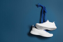 Pair Of Stylish Shoes With Laces Hanging On Blue Wall, Space For Text