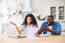 Anxious Mixed Race Couple Looking Through Domestic Bills, Reading Papers At Home, Worried Biracial Wife And African Husband Calculating Family Budget,not Enough Money On Bank Account To Repay The Loan