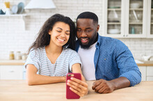 Lovely Multiracial Couple Taking A Selfie Together Sitting At The Kitchen Desk, Smiling Biracial Woman And Cheerful African Guy Hold Smartphone, Look At The Webcam. Couple Is Web Surfing On The Phone