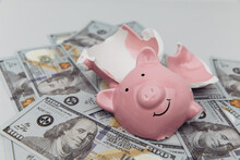 Investment And Bankruptcy Concept. Broken Piggy Bank On Dollar Banknotes Close-up