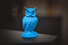 An Owl Made On A 3d Printer Stands On A Blurry Dark Background