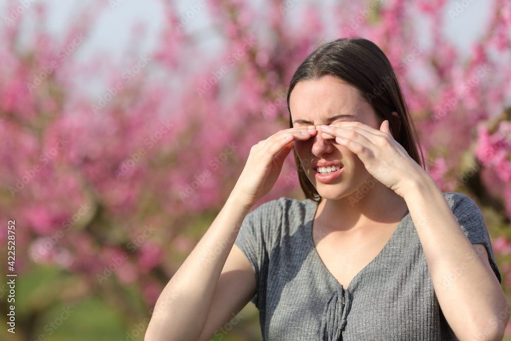 Fototapeta Woman scratching itchy eyes in spring in a flowers field