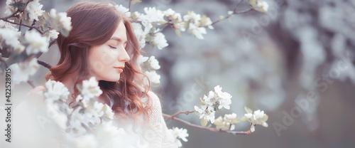 Obraz na płótnie springtime fashion portrait of a young girl in a blooming cherry garden, tendern