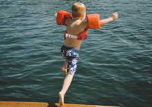 A Child Jumping Off A Dock Into A Blue Lake.