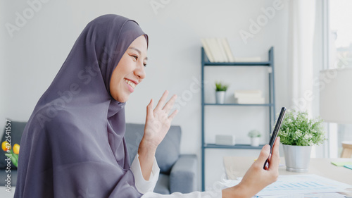 Fototapeta Young Asia muslim businesswoman using smart phone talk to friend by videochat brainstorm online meeting while remotely work from home at living room. Social distancing, quarantine for corona virus. obraz