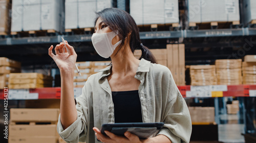 Fotografie, Tablou Young Asia businesswoman manager wear face mask looking for goods using digital tablet checking inventory levels stand in retail shopping center