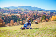 Happy Woman Sitting In The Mountains With Meadow And Colorful Trees On Backdrop. Beautiful Autumn Background. Girl Enjoy Fall In National Natural Park Synevir, Carpathian Mountains, Ukraine.