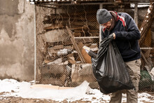 Poor Homeless Man With Trash Bag Outdoors On Winter Day