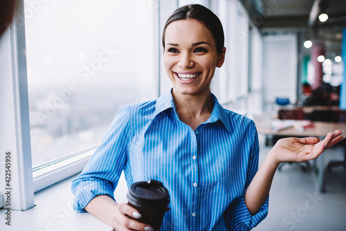 Fototapeta Cheerful Caucaisan secretary with disposable caffeine beverage laughing in cowor