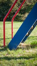 Escalera De Tobogán Rojo, Amarillo Y Azul En Parque De Hierba Verde