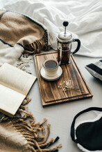 Open Book In Bed With Coffee Brewed In A French Press And Cup On A Wooden Board. Morning At Home, Coziness And Comfort.