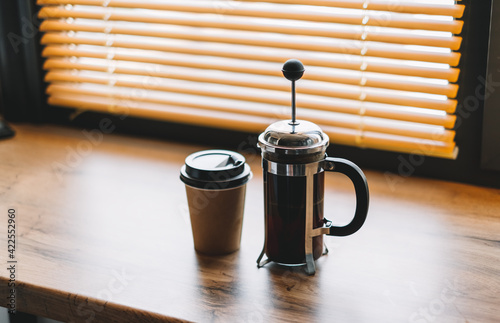 Canvas Coffee brewed in a french press and paper cup on a wooden table near window
