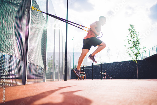 Obraz Energetic man exercising on sports ground - fototapety do salonu