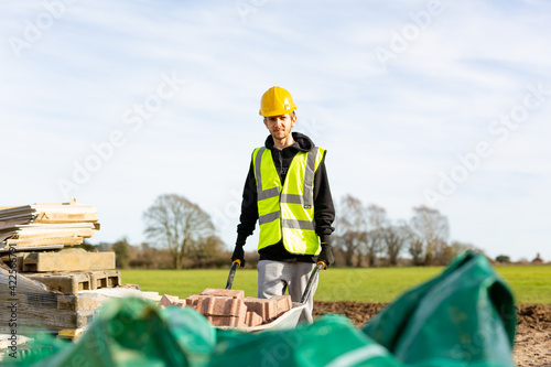 Foto A young adult male builder wearing a high visibility vest and hard hat pushing a