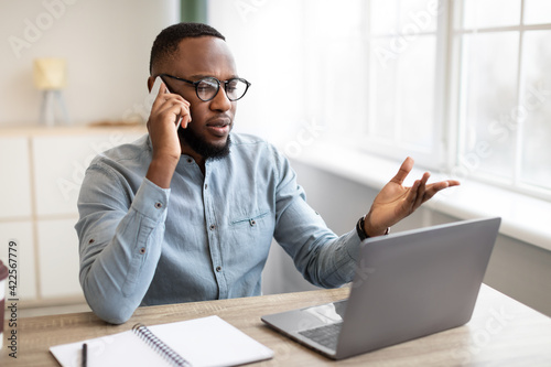 Serious Black Businessman Talking On Mobile Phone Sitting In Office