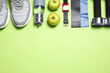 canvas print picture - Fitness equipment, apples and water on green background, flat lay. Space for text