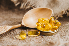 Fish Oil Capsules On A Wooden Spoon. Fish Oil Pills, Tablets On The Burlap. Vitamin Complex Omega 3,6,9. Fish Oil Capsules With Omega-3, Vitamin D. Close Up