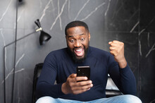 Goal Achievement. Overjoyed African-American Businessman Looks At The Smartphone Screen And Rejoices, Happy With Unexpected Opportunity Black Guy Scream Yes, Received Promotion, Won In Video Game