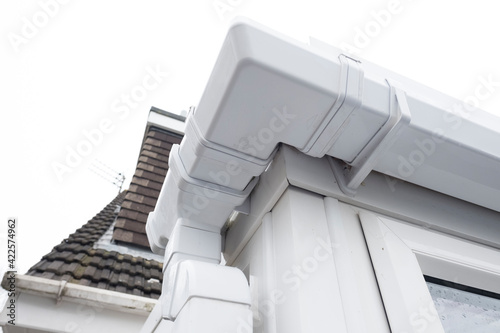 Fotografia, Obraz Cleaned white plastic pvc gutters and drain pipes that were blocked and full of green mould on the plastic fascias