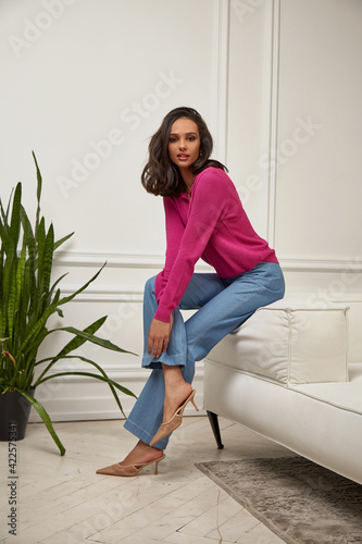Canvas Print Fashion beautiful model sexy pretty lady dark tanned skin woman brunette hair wear denim jeans clothes casual office style or romantic date or party in decoration designer room home or hotel