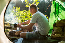 Man Making Coffee In Camping Kettle On Campfire In Forest On Shore Of A Lake, Sitting In Tent, Making A Fire, Grilling. Happy Isolation Concept. Exploring Finland. Scandinavian Landscape.