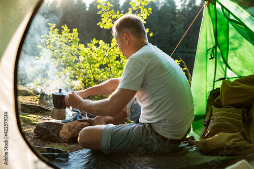 Obraz na plátně Man making coffee in camping kettle on campfire in forest on shore of a lake, sitting in tent, making a fire, grilling