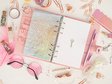 Silver Key On The White Page Of The Planner. Diary Open With White And Holographic Page. Pink Planner With Cute Stationery. Top View Of The Pink Planner With Stationery. Pink Glamour Planner