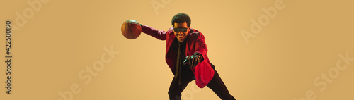 Fototapeta High-fashion styled man in red jacket playing basketball isolted over brown background obraz