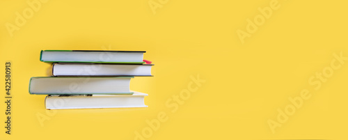 Fototapeta A stack of books on a yellow background. The books are on a plain background with space for writing. Composition of a reading person. obraz