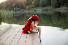 Caucasian Cute Girl In A Coat And Hat On The Footpath By The Lake, Happy Childhood In Nature, Child Playing In The Park Near The Water