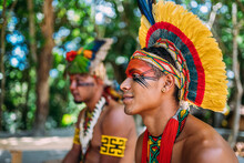 Two Indians From The Pataxó Tribe. Brazilian Indian From Southern Bahia With Feather Headdress, Necklace And Traditional Facial Paintings Looking To The Left